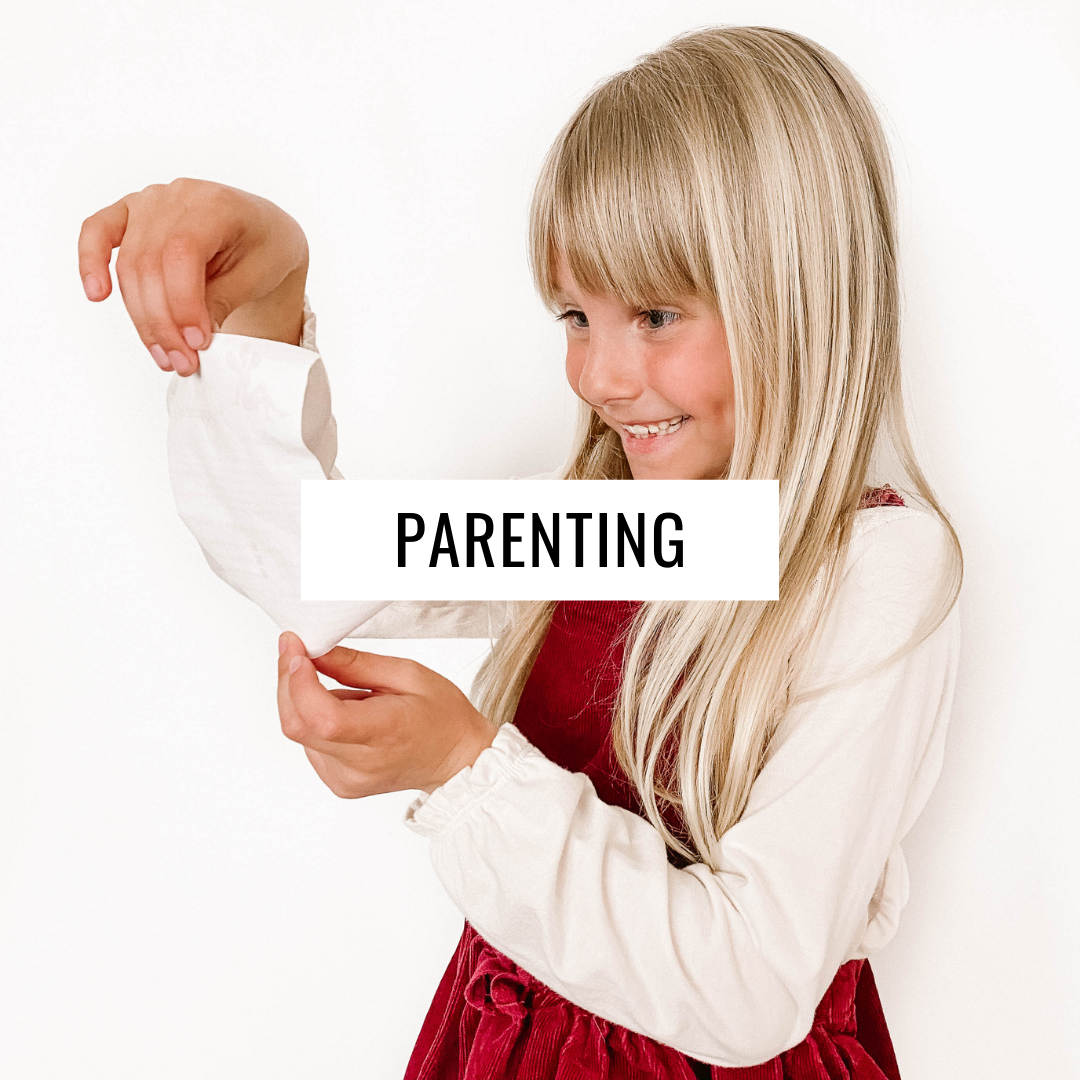 Girl smiles while reading a small note with text overlay - Parenting.
